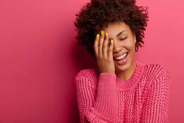Une femme à la peau sombre couvre la moitié du visage, rit avec un sourire à pleines dents