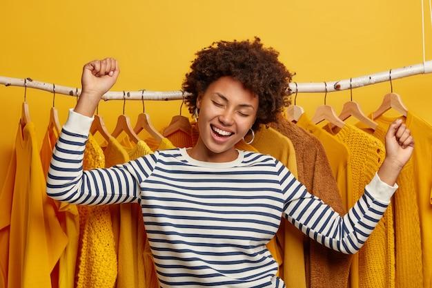 Une femme à la peau sombre positive et insouciante danse joyeusement, pose près de porte-vêtements, se réjouit de la journée et des achats réussis, vêtue d'un pull rayé