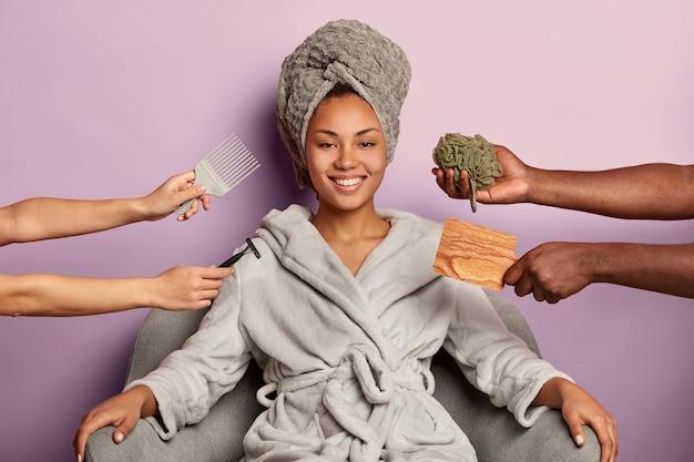 Femme à la peau sombre positive avec un sourire à pleines dents, porte une serviette sur la tête et un peignoir