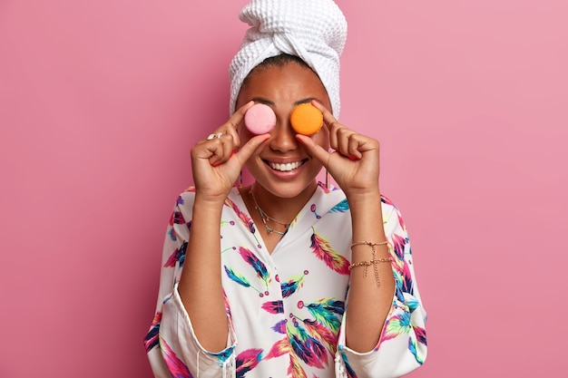 Une femme à la peau sombre et souriante positive couvre les yeux de délicieux macarons sucrés, reçoit des calories, aime manger des aliments sucrés, porte une serviette de bain sur la tête, une robe domestique décontractée. concept de femmes et de régimes amaigrissants