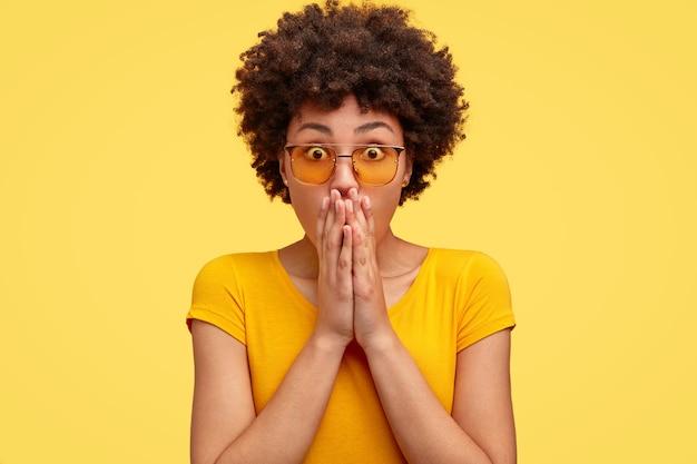 Femme à la peau sombre surprise émotionnelle avec une expression stupéfaite, couvre la bouche avec les deux mains