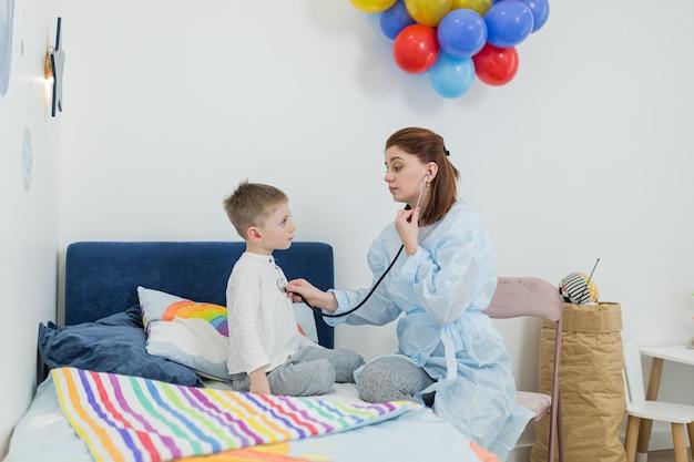 Femme pédiatre examinant un petit garçon malade à son domicile, essayant de divertir et de remonter le moral du patient