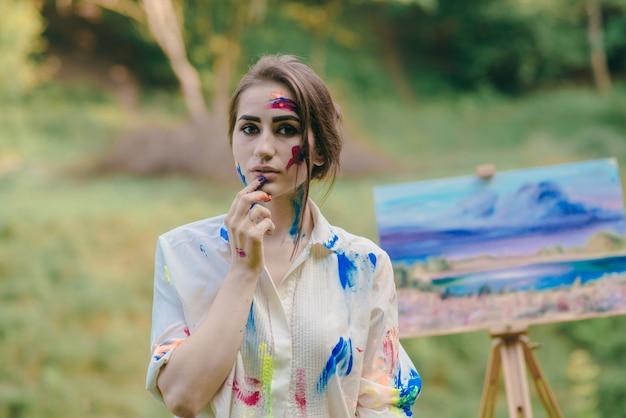 Femme peignant une lèvre avec une photo à ses côtés