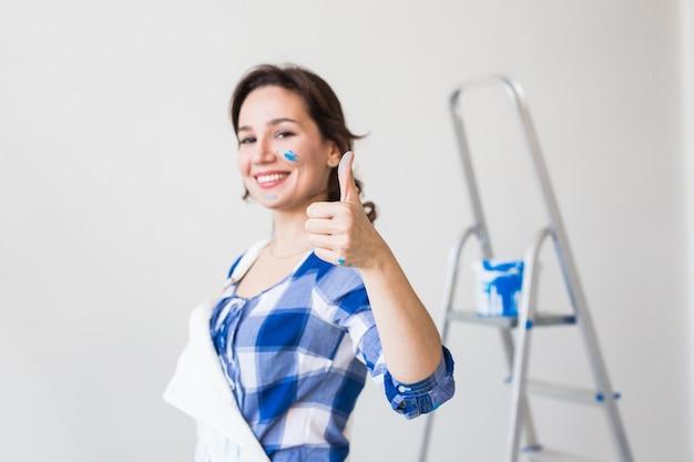 Femme peignant le mur et a l'air très heureuse, elle montre le pouce vers le haut