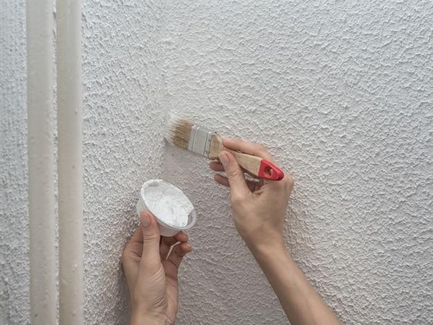 Femme peignant le mur. restauration des murs blancs peints.