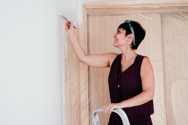 Femme peignant les murs de la chambre