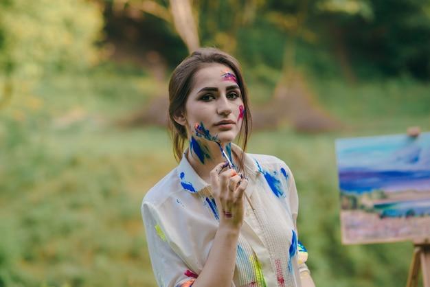 Femme peignant sa joue en bleu avec un pinceau