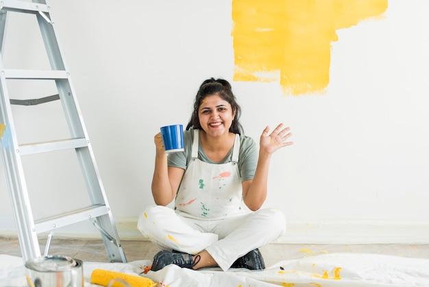 Femme peignant ses murs jaune