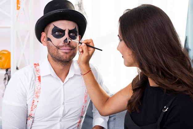 Femme peignant son homme pour halloween