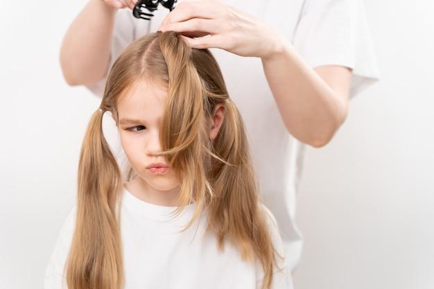 La femme peigne et fait les cheveux d'une petite fille sur le blanc