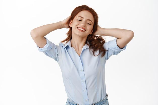 Femme, peigner les cheveux roux et souriant avec les yeux fermés, faire une pause, se reposer et profiter de ses loisirs, debout sur blanc