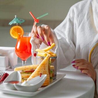 Femme en peignoir ayant un repas, manger des frites.