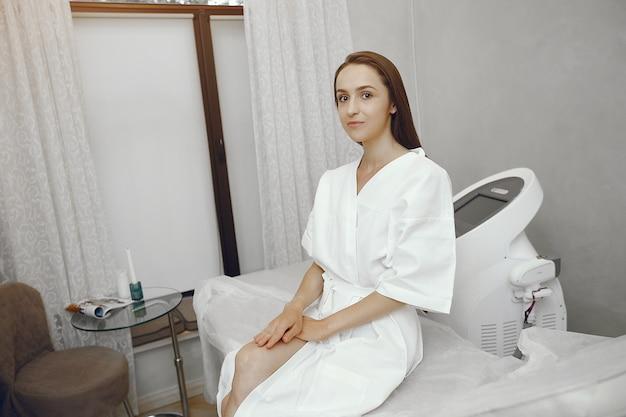 Femme en peignoir blanc dans un studio de cosmétologie