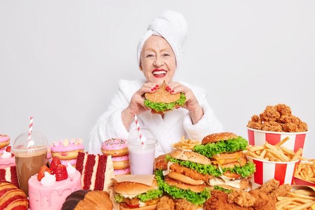 Une femme en peignoir blanc et une serviette enroulée sur la tête mange un délicieux hamburger a un jour de repas de triche se permet de manger des aliments riches en calories sur blanc