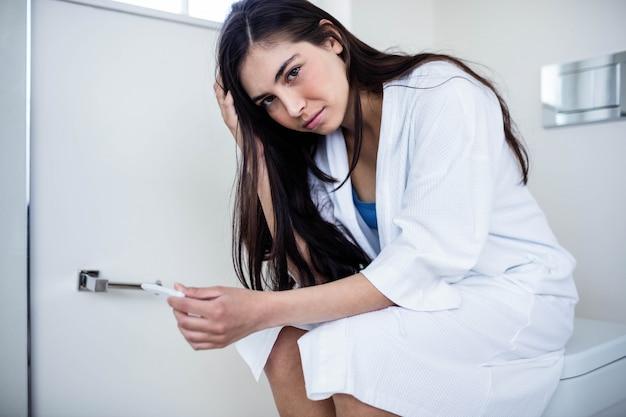 Femme, peignoir, regarder, elle, test enceinte, dans, toilette