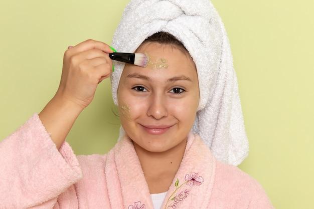 Femme en peignoir rose faisant du maquillage