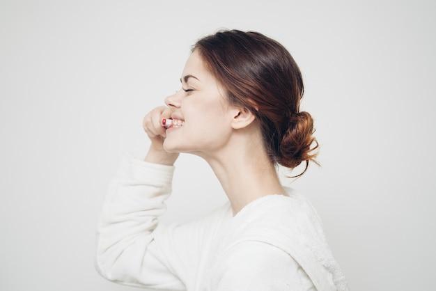 Femme en peignoir se brosser les dents
