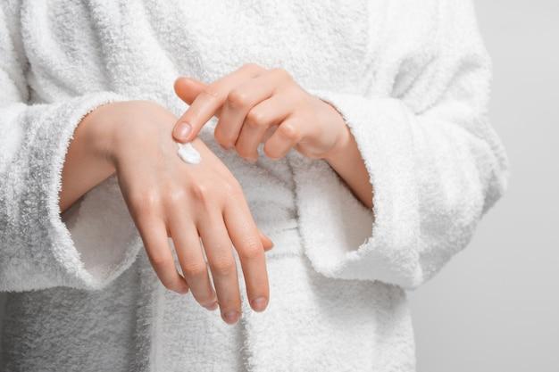 Une femme en peignoir se couvre les mains d'une crème hydratante.