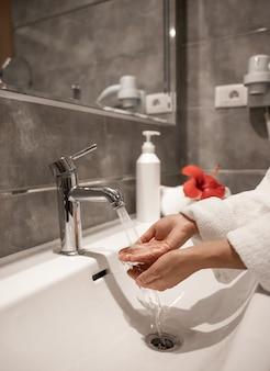 Une femme en peignoir se lave les mains sous l'eau courante d'un robinet.