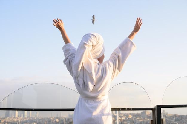 Femme en peignoir sur la terrasse d'une maison au lever du soleil