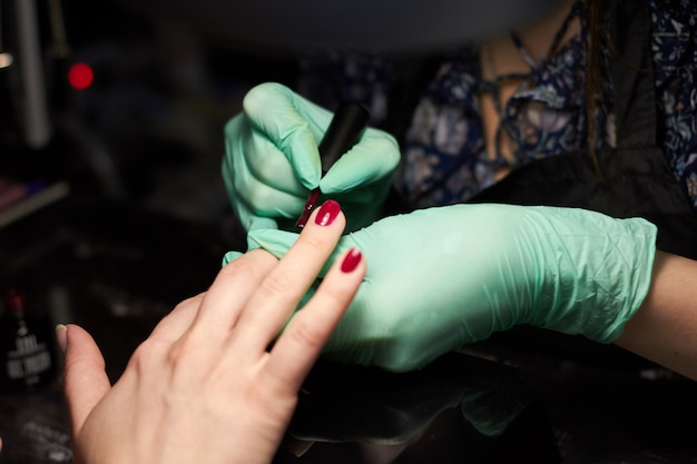 Femme peindre un client. ongles manucure soins des mains