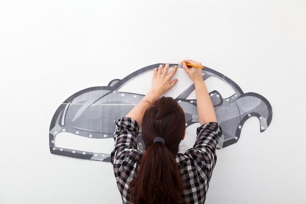 Femme peindre une petite voiture