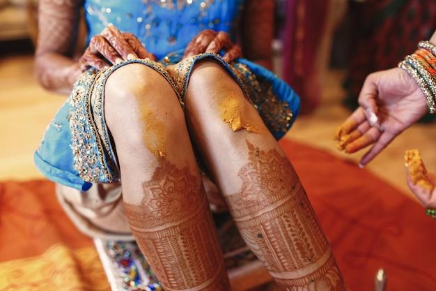 Femme peint les genoux de la mariée avec du curcuma