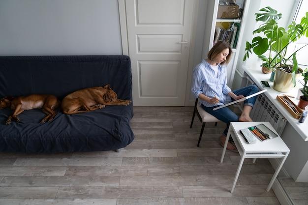 Femme peint une image sur toile fait des croquis au crayon assis près de la fenêtre à la maison pendant le verrouillage