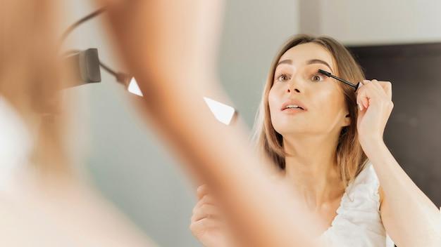 La femme peint ses cils regardant dans un miroir dans un salon de beauté
