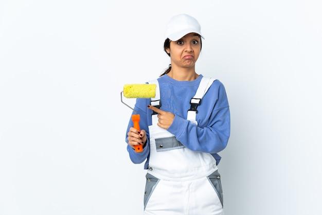 Femme peintre sur blanc isolé pointant vers les latéraux ayant des doutes