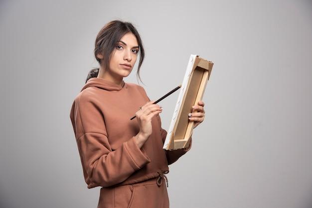 Femme peintre dessin sur châssis avec pinceau