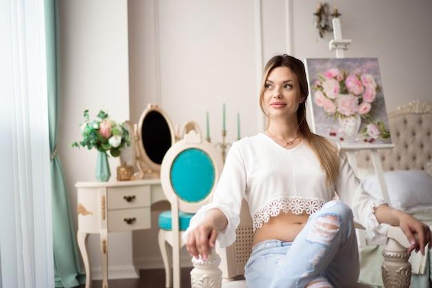 Femme peintre enceinte dessin en studio d'art à l'aide de chevalet. portrait d'une jeune femme pragnant peinture avec des peintures à l'huile sur toile blanche, portrait vue de côté