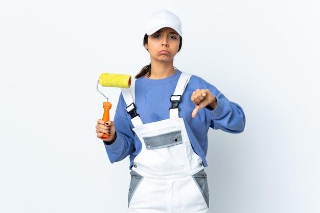 Femme peintre sur fond blanc isolé montrant le pouce vers le bas avec une expression négative