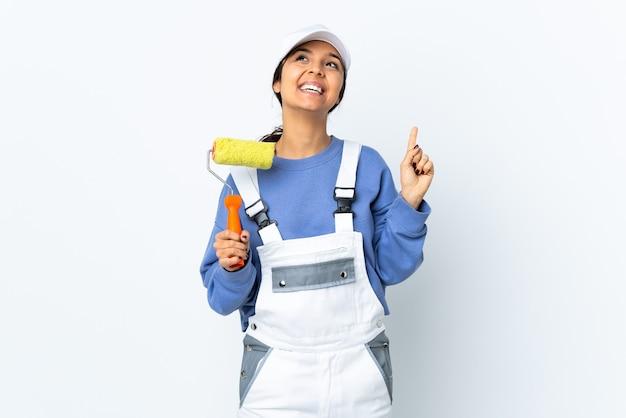 Femme peintre sur fond blanc isolé pointant vers le haut et surpris