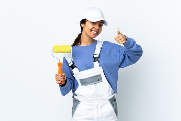 Femme peintre sur mur blanc isolé donnant un geste de pouce en l'air