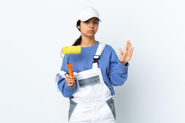 Femme peintre sur mur blanc isolé faisant le geste d'arrêt