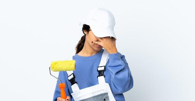 Femme peintre sur mur blanc isolé avec maux de tête