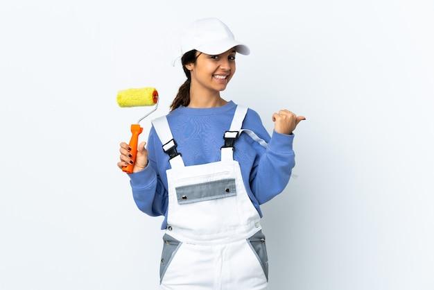 Femme peintre sur mur blanc isolé pointant vers le côté pour présenter un produit