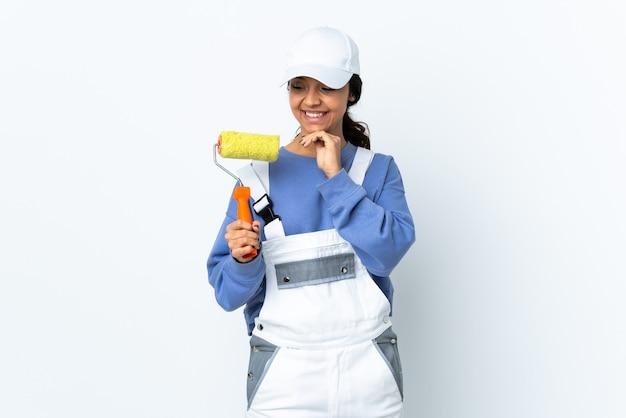 Femme peintre sur mur blanc isolé à la recherche sur le côté et souriant