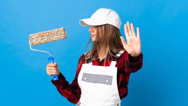 Femme peintre sur mur bleu faisant un geste d'arrêt et déçu