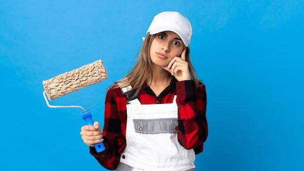Femme peintre sur mur bleu isolé pensant une idée