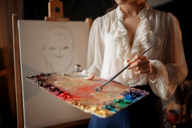 Femme peintre avec palette de couleurs et pinceau debout contre chevalet en studio. peinture créative, femme dessin croquis au crayon, intérieur de l'atelier sur fond
