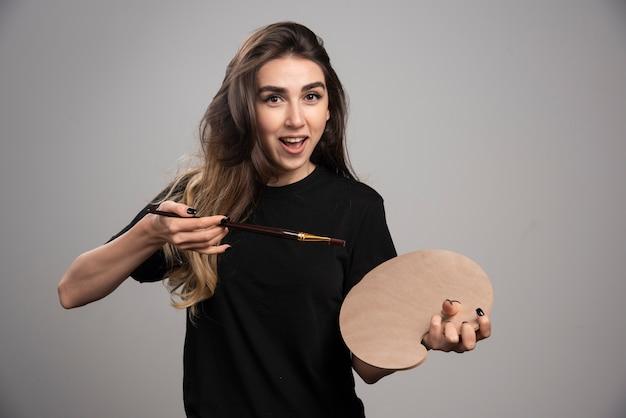 Femme peintre posant avec une palette vide et un pinceau.