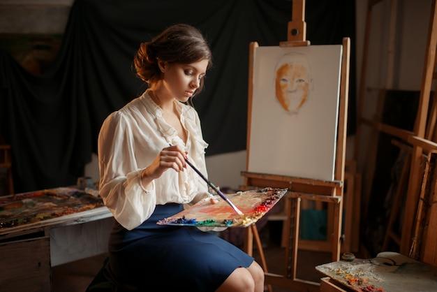 Femme peintre tient la palette de couleurs et le pinceau