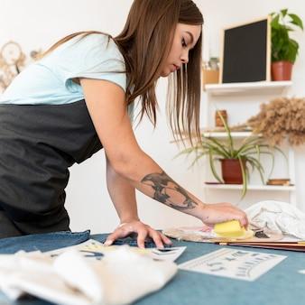 Femme peinture jeans avec éponge