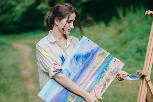 Femme avec de la peinture tachée t-shirt avec une image dans sa main