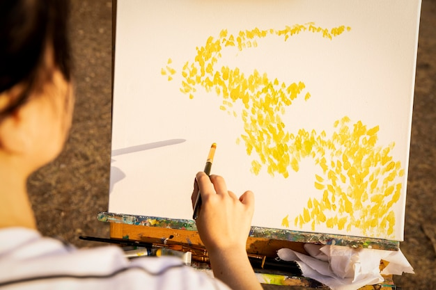 Femme peinture sur toile à l'extérieur dans la nature