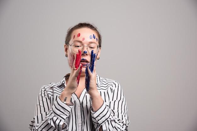 Femme avec des peintures sur son visage et des lunettes sur fond gris