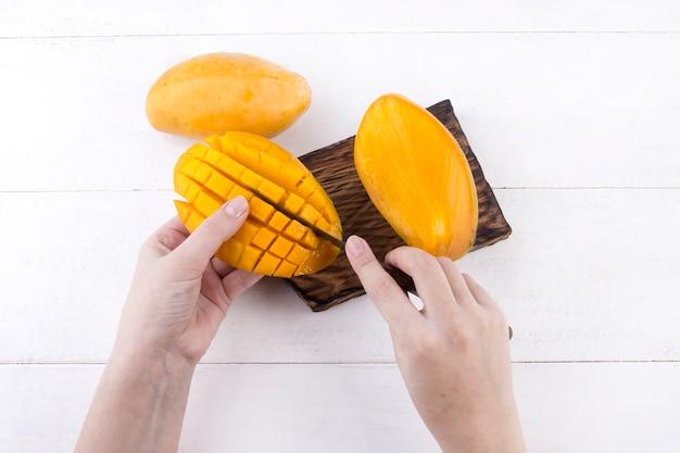 Femme peler de délicieuses mangues jaunes mûres avec un couteau sur fond blanc