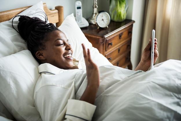Une femme pendant un appel vidéo au lit